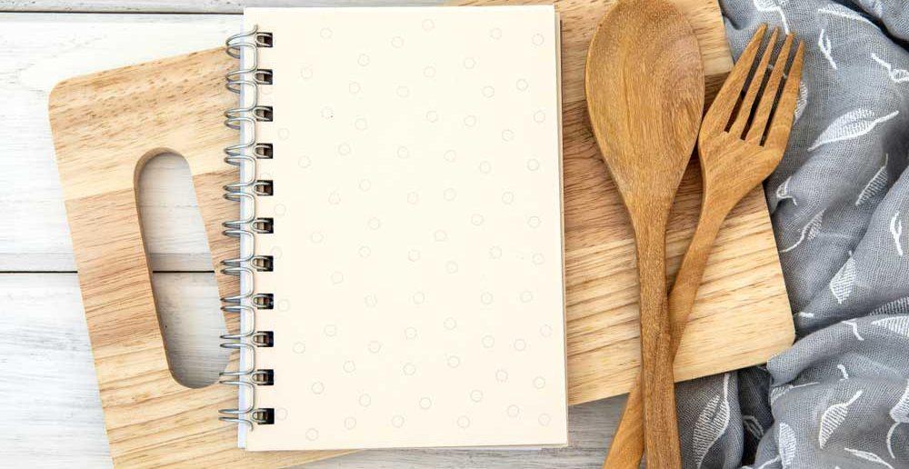 Leg een kookboek op een snijplank in de keuken